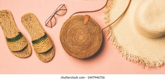 Summer apparel items. Flat-lay of summer flip flops, sunglasses, straw sunhat€ and wicker round shoulder bag over pastel pink background, top view, wide composition. Summer beach vacation concept