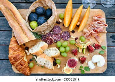 Summer appetizer in French Riviera with plate full of fruits, bread, cheese and ham