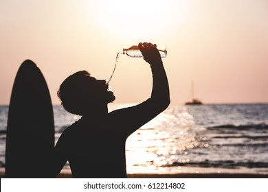Summer - Asian men drink water from a water bottle at Sunset after surfboarding silhouette.