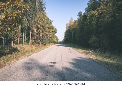 summer asphalt road in perspective with signs and markings, green forest on both sides - vintage retro look