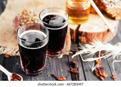 summer and autumn cooling drink , kvass or  dark beer with honey , raisins and rye bread on a wooden background