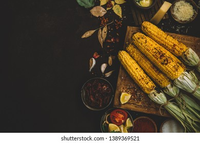 Summer or autumn food background. Ideas for barbecue and grill parties. Grilled corn, cheese on a dark wooden table. Healthy food, organic, bio, homemade food. Copy space, top view.