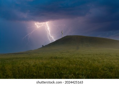 Summer awe landscape with flashes of bright lightning on dark cloudy sky during a thunderstorm over the Orthodox cross at the top of the hill. Drokinskaya mountain near Krasnoyarsk, Russia