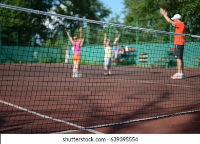 Summer background - blurred active kids playing sports on the tennis court.