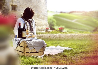 summer background of blurred flowers and woman and wine on box