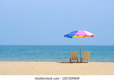 Summer background, chair and colorful umbrella on beach and sea background with copy space