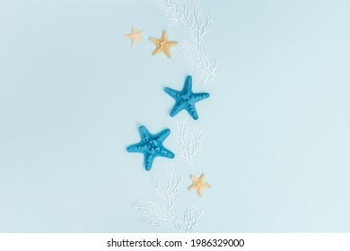 Summer background with colorful seastar and white coral on pastel blue. Concept of travel and vacation. Flat lay, top view, copy space