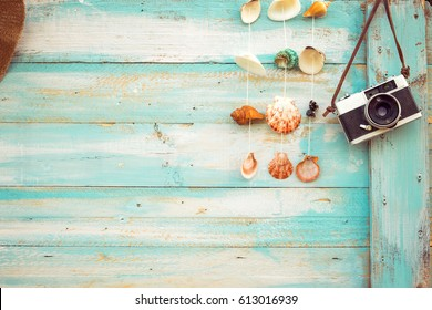 Summer background - The concept of leisure travel in the summer on a tropical beach seaside. retro camera with shell decoration hanging on wood wall background.  vintage color tone styles.