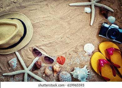 summer background frame,sandal beach,hat,sunglasses camera and starfish on sand