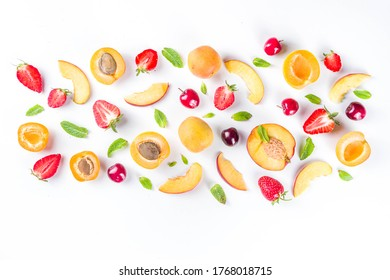 Summer background with fresh fruits and berries on white background. Set of various seasonal fruit and berry  - strawberry, apricots, peach slices, cherry, mint. Flat lay. Summer fruits concept.  - Shutterstock ID 1768018715
