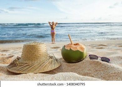 Summer background. Girl in defocus out of the ocean. on the sand lies her hat, sunglasses and a coconut.