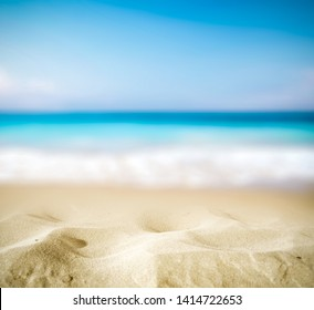 Summer background of hot sand with free space for your decoration and blurred background of ocean with summer sun light.