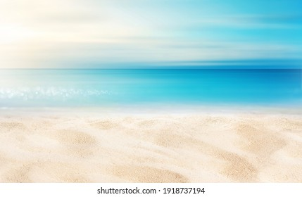 Summer background image of tropical beach with blurred horizon at sunset. Light sand of beach against backdrop of sparkling ocean water. Natural seascape.