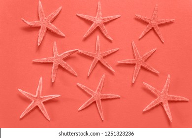 Summer background of paper with starfish in color of the year 2019 Living Coral pantone