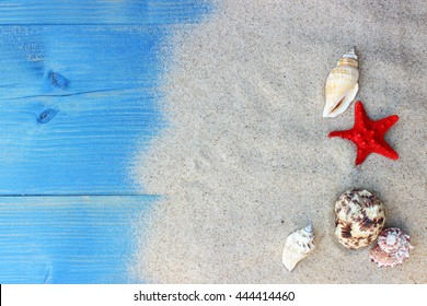 Summer background with sea shells and red star with sand on blue wooden planks. Copy space. Marine theme