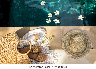 Summer background with straw hat, flip flops, wicker bag, white cotton towel and glass bottle with still water near the swimming pool. Summer holiday trendy concept. Top view.