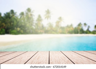 Summer background top table wood plank and blurred tropical beach with coconut tree an d blue sea.