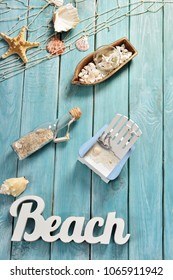 summer background with top view of beach accessories and letters on blue wooden board