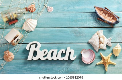 summer background with top view of beach accessories and letters on blue wooden board with copy space for own text