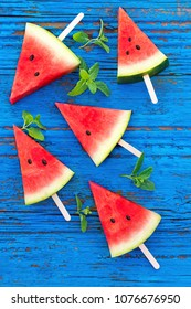 Summer background. Watermelon fruit slice popsicles on a  blue wood background with mint leaves, flat lay