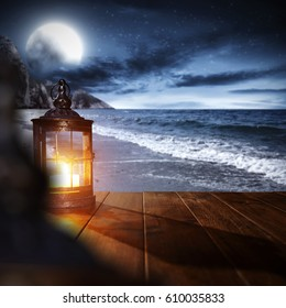Summer background of wooden table on beach and lamps with light and landscape of sea with moon on sky  - Shutterstock ID 610035833