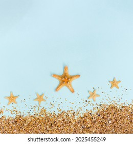 Summer background with yellow seastar and sand on pastel blue. Concept of travel and vacation. Flat lay, top view, copy space