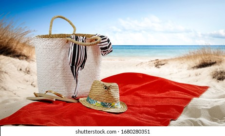 Summer bag on red towel on beach and free space for your decoration.