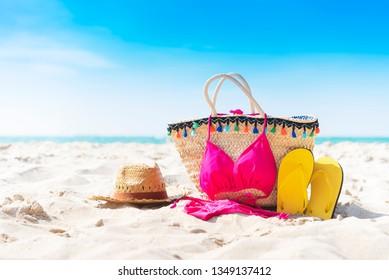 Summer bag, slipper, hat and bikini on the tropical beach with blue sky background.