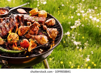 Summer barbecue cooking over a hot fire with assorted vegetables, T-bone steak and spicy chicken legs sizzling on the grill in a green meadow