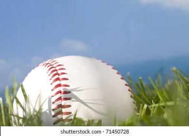 Summer baseball concept with a baseball in the outfield grass against a perfect blue sky.