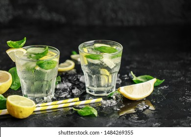 Summer basil lemonade on dark stone background. Fresh summer cocktail with basil, lemon and ice cubes. Homemade fresh lemonade with lemon and basil. Food and drink concept