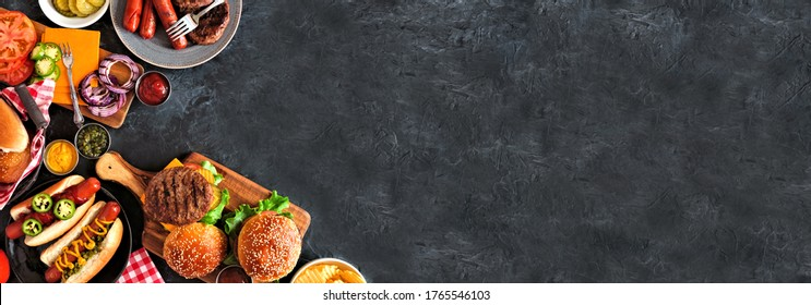 Summer BBQ food corner border with hot dog and hamburger buffet. Top down view over a dark slate banner background. Copy space.