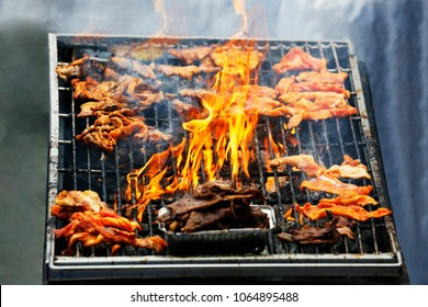 Summer BBQ grilling marinated pork on fire, traditional Korean style. Korean barbecue is Korean style grilling meat, usually use thinly sliced traditionally marinated and unmarinated meat dishes.