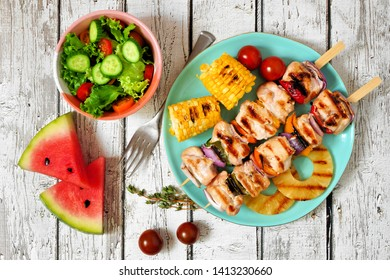 Summer BBQ or picnic food concept. Salad, grilled kabobs, corn and fruit. Top view table scene over a white wood background.