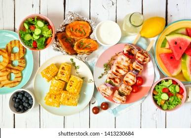 BBQ d'été ou concept de nourriture pique-nique. Sélection de fruits, salade, grillades de viande et de pommes de terre. Vue de dessus, scène de table sur fond blanc bois.