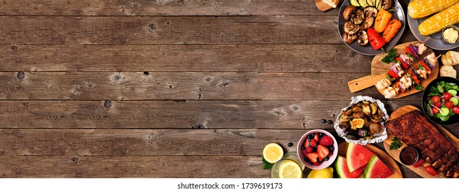 Le BBQ d'été ou coin pique-nique bordent une bannière rustique en bois. Viandes grillées assaisonnées, légumes, fruits, salade et pommes de terre. Vue de dessus avec espace de copie.