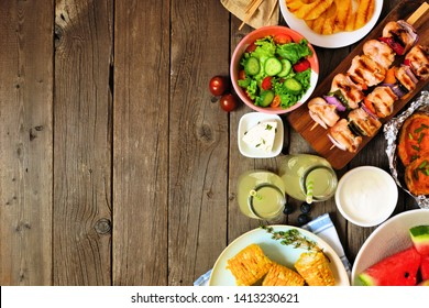 Summer BBQ or picnic food side border. Selection of grilled meat, fruits, salad and potatoes. Top view over a rustic wood background. Copy space.