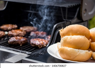 Summer BBQ - smoking hamburgers with buns on the side.