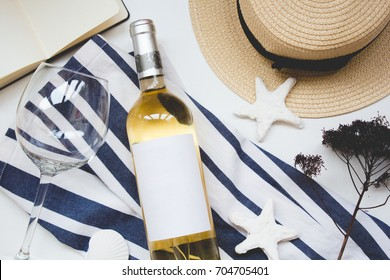 Summer beach accessories for sea holiday: straw hat, wine and shell, flower and striped dress. Flat lay on the white background. Feminine desk top view, vacation concept for design site and beauty