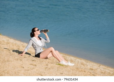 Summer beach active woman drink water bottle in fitness outfit