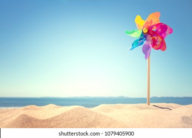 Summer beach background, pinwheel or windmill in the sand concept for vacation copy or message