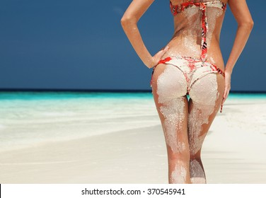 Summer beach concept. Sandy woman buttocks on the beach background. Sexy summer woman body. White sand, blue sky and crystal sea of tropical beach. Vacation at Paradise. Ocean beach relax, travel.
