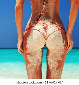 Summer beach concept. Sexy woman buttocks on blue sea and blue sky background, sandy woman buttocks on the beach background. Sexy tanned summer woman body