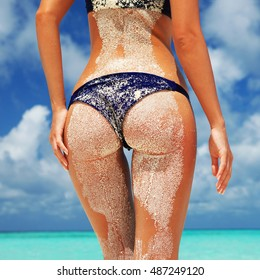 Summer beach concept. Sexy woman buttocks on blue sea and blue cloudy sky background, sandy woman buttocks on the beach background. Sexy summer woman body