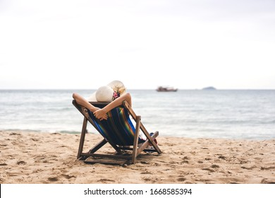 Summer beach holiday concept. Young asian woman relax on beach chair arm up her hand with floppy hat. White sand cler sky background with copy space. Pattaya, Thailand