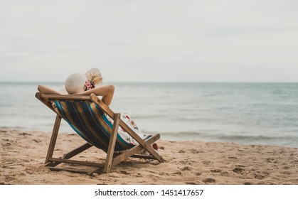Summer beach holiday, Young asia woman relaxing on beach chair arm up her hand with floppy hat At Pattaya, Thailand