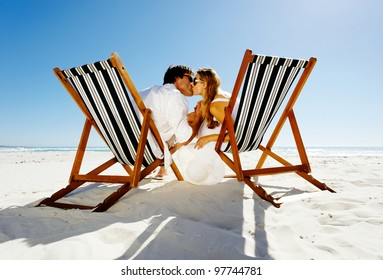 Summer beach kissing couple sitting on deck chairs enjoying an intimate moment