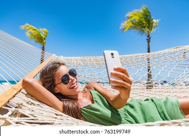Summer beach lifestyle young woman using phone app texting on smartphone relaxing at tropical Caribbean resort on hammock. Mobile wifi internet on travel holidays. Vacation fun.