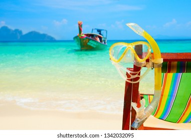 Summer beach paradise, diving mask and snorkel on a wooden chair on the background of a boat with divers. Phi Phi island, Thailand