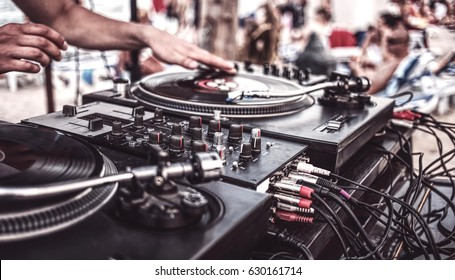 Summer beach party. DJ plays vinyl records, side view. Raving funs around the scene